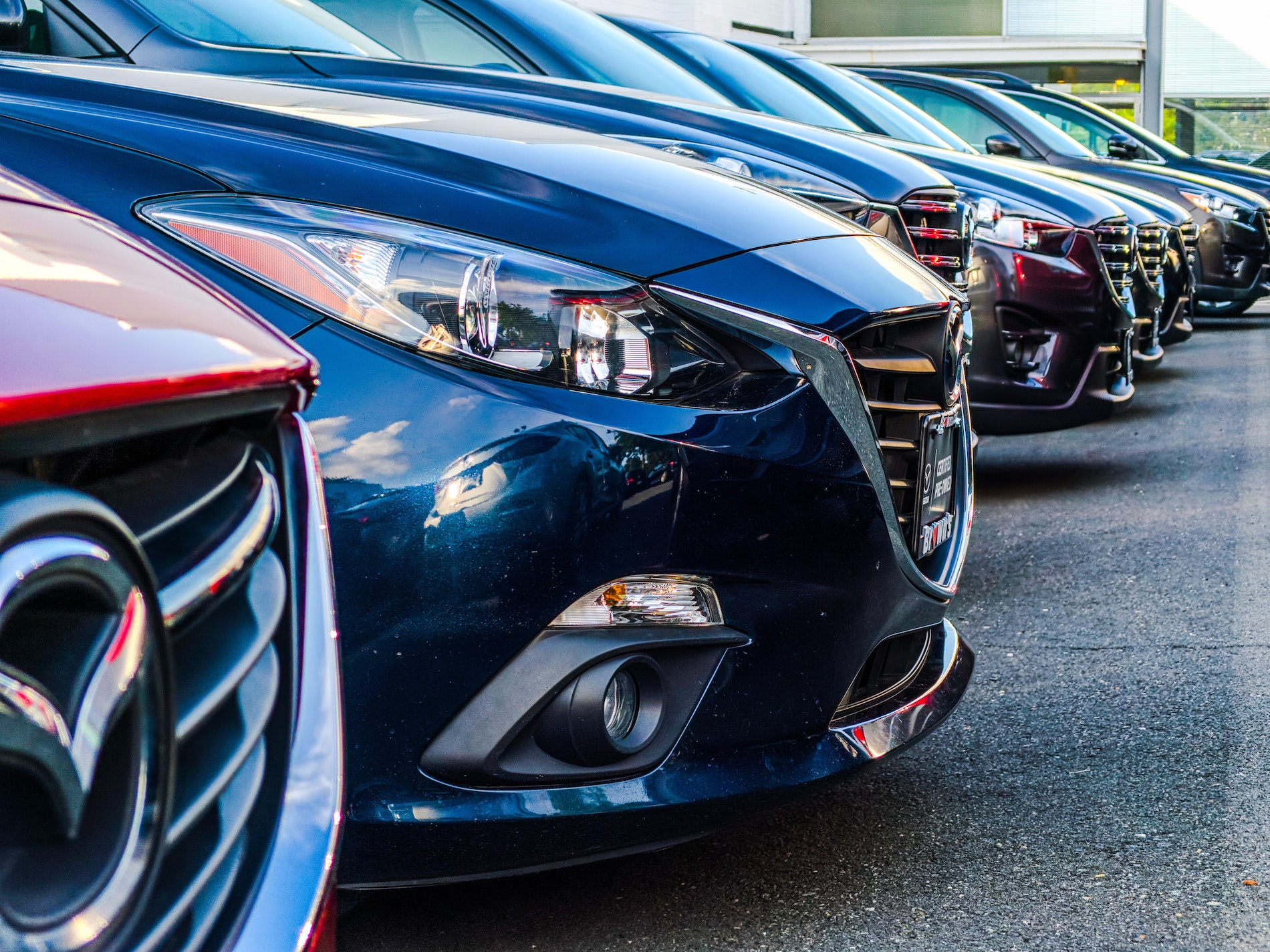 cars lined up at a car dealership that processing payments via ach