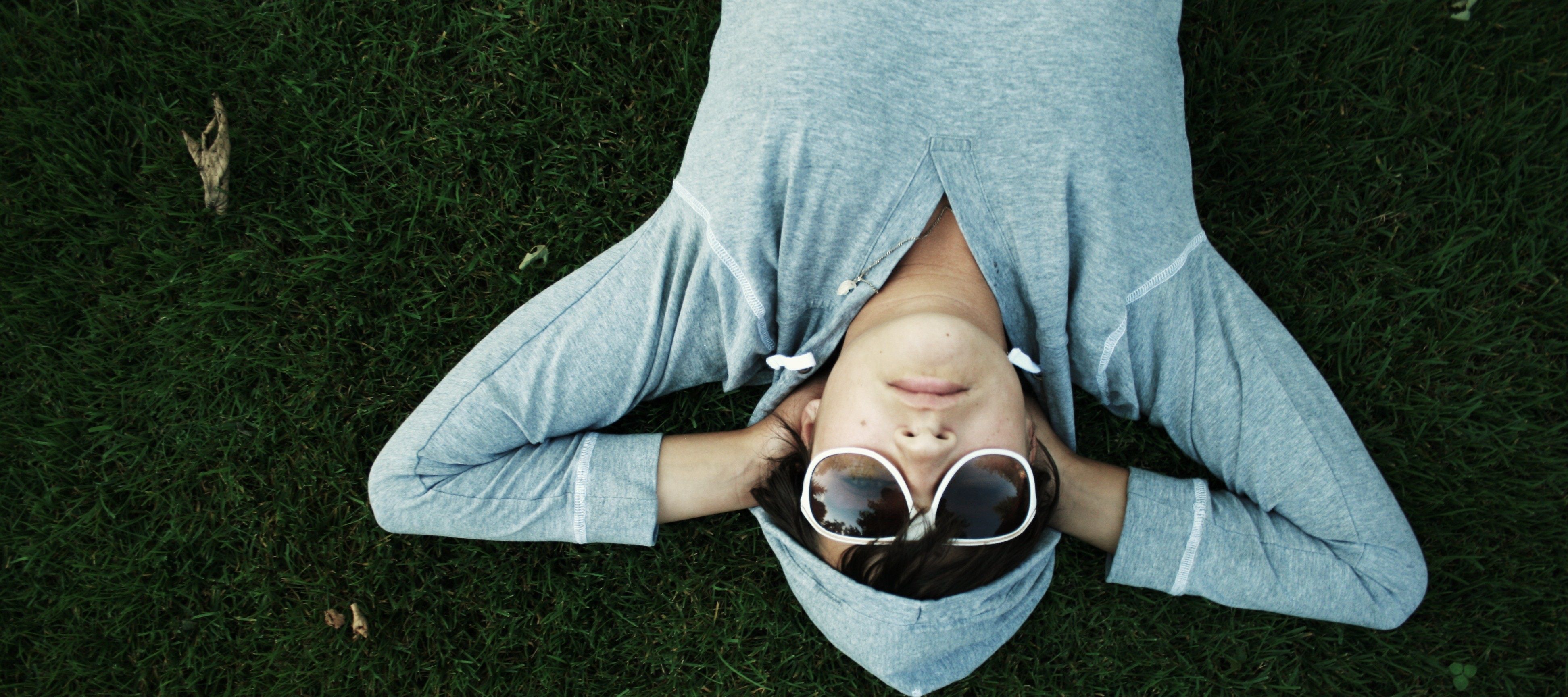 person laying on ground in hoodie and sunglasses