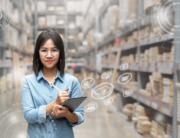 woman-holding-tablet-and-stylus-in-warehouse-with-cardboard-boxes-on-shelves-and-digital-overlay-of-online-shopping-icons