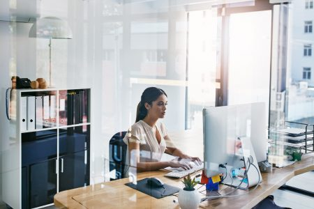 A woman in an office with clear walls is sitting at a desk and working on a computer