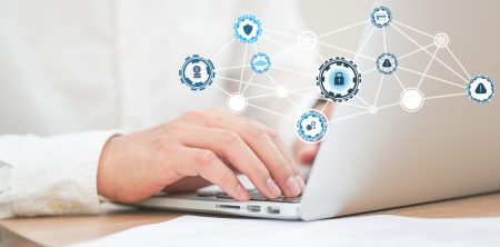 hands typing on a white laptop with a network of data security and management icons.